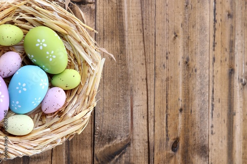 Easter eggs in nest on color wooden background Poster