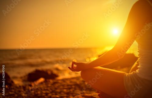 Foto  Hand der Frau in einem Yoga-Pose zu meditieren am Strand bei Sonnenuntergang