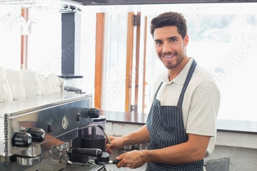 Fotografie, Obraz  Smiling barista preparing espresso at coffee shop