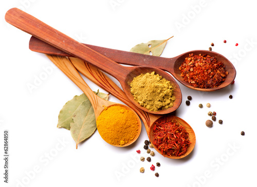 Photo Stands Spices Spices and herbs. Curry, saffron, turmeric, cinnamon over white
