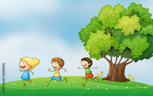 Three energetic kids playing at the hilltop with a big tree