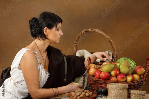 Fotografering  Young Romana peeling the onion with basket full of fruits and ve