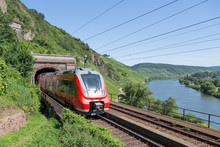 Train Leaving A Tunnel Along River Moselle In Germany