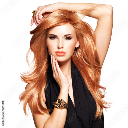 Obraz na płótnie Beautiful woman with long straight red hair in a black dress.