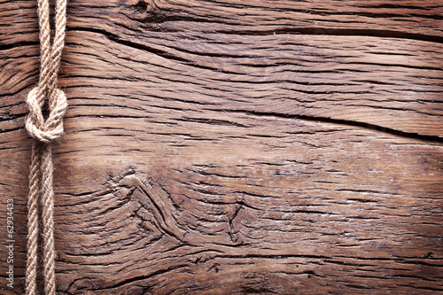 Photo Stands Ship Sailor's knot over old wooden background.