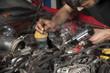 Car mechanic melting solder wire on soldering iron tip