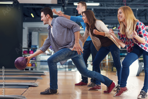 Foto Friends cheering their friend while throwing bowling ball