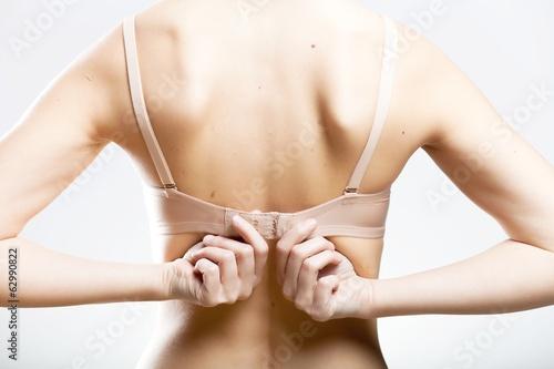 Obraz Wearing bra closeup, unhooking the clasp - fototapety do salonu
