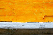 A Close Up Veiw Of The Paint On A Wooden Boat.