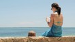Beautiful woman taking picture with smartphone by the sea