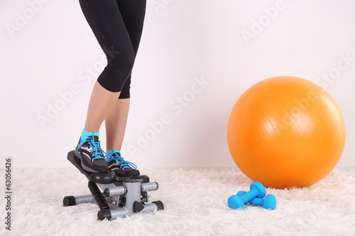 Fotografie, Obraz  Young beautiful fitness girl exercising on stepper in gym