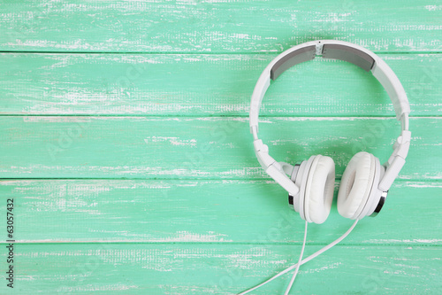 Photo  White headphones on wooden table close-up