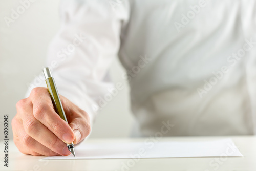 Valokuva  Man writing with a fountain pen on blank paper