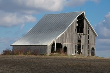Decaying Barn In Barren Field With Blue Sky