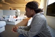 Women Sitting On Beds In Homeless Shelter