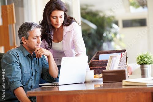 Fotografía  Worried Hispanic Couple Using Laptop On Desk At Home