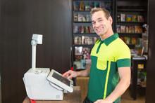 Cashier At Cash Register In Shop Or Store