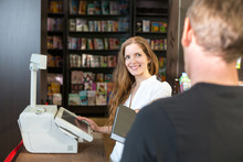 Cashier In Bookstore Serving A...