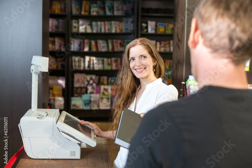 Photographie  Cashier in bookstore serving a customer or client