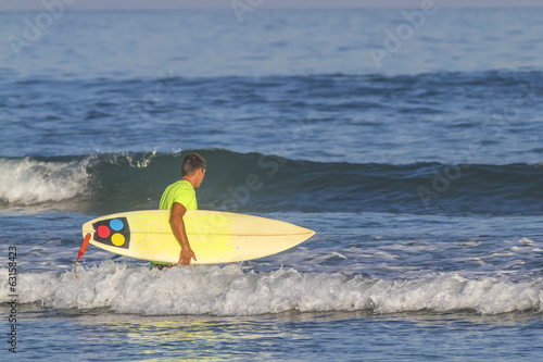 Poster Nautique motorise Surfer with his surfboard at the Balanfan beach.Bali.Indonesia