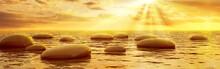 Stones Reflecting In Water Under Sun Beams