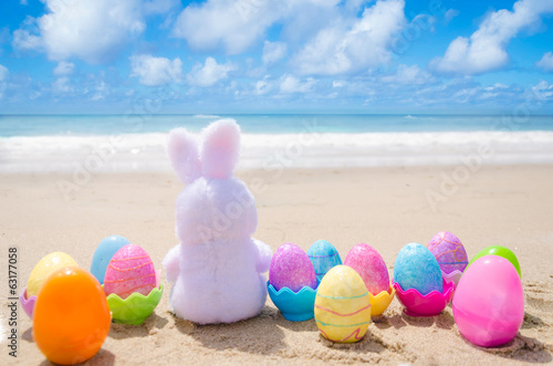 Photo  Easter bunny and color eggs on the beach