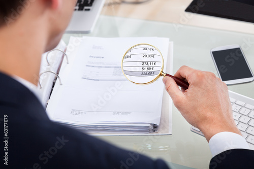 Fotografie, Tablou  Auditor Examining Invoice With Magnifier