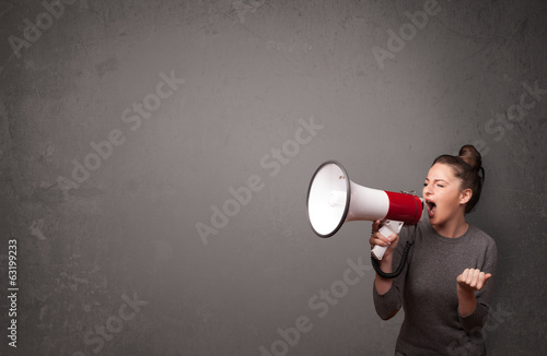 Fotografía Muchacha que grita en el megáfono sobre el fondo del espacio de copia