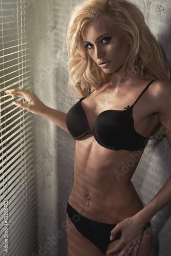 Fototapeta Młoda seksowna kobieta w czarnej bieliźnie w tle okna ścienna