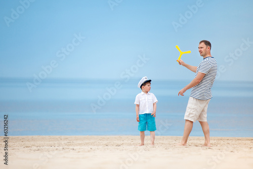Father and son playing together on the beach Poster