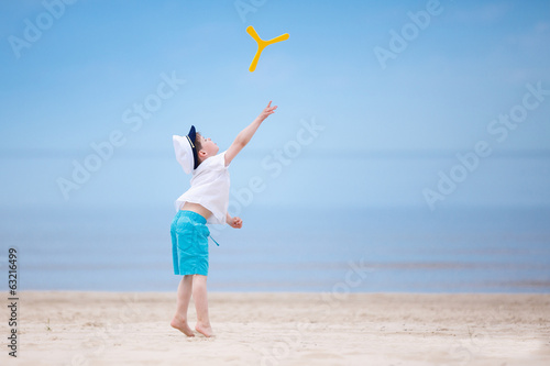 фотография  Happy little boy playing on tropical beach