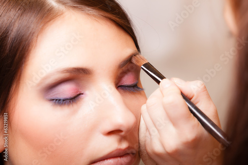 Fotografía  Makeup artist applying with brush cosmetic on eyebrow of woman