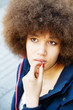 Thoughtful woman with afro hair cut