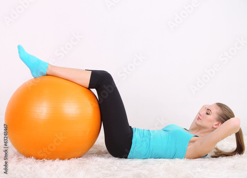 Young beautiful fitness girl exercising with orange ball in gym