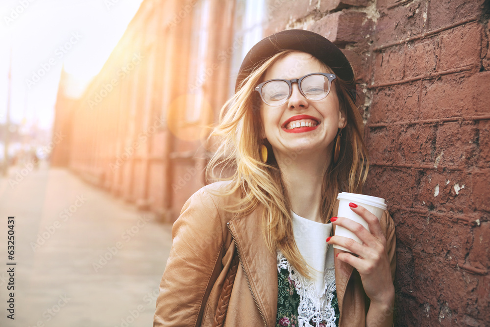 Fototapeta Cheerful woman in the street drinking morning coffee in sunshine