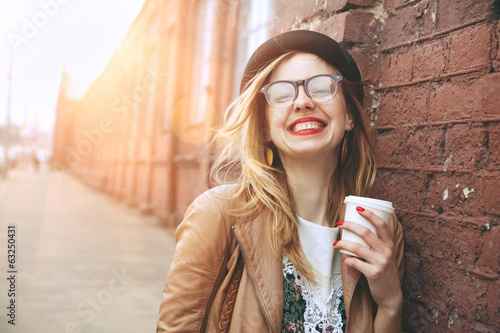 Cheerful woman in the street drinking morning coffee in sunshine Fototapeta