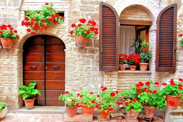 Obraz na Szkle Uliczki Italian house front with colorful potted flowers