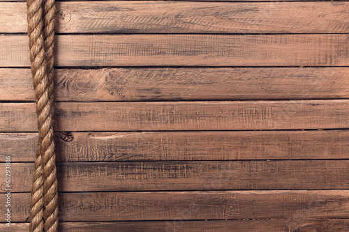 Tuinposter Schip Rope on old wooden board vertical