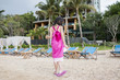 kid in pink walking on the beach