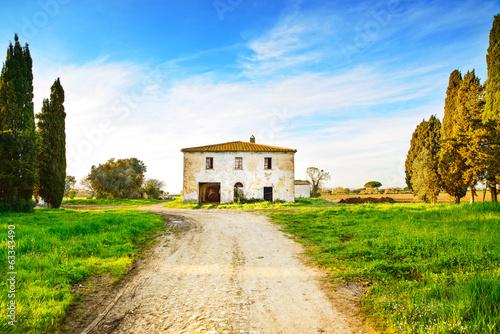 stary-zaniechany-wiejski-dom-droga-i-drzewa-na-zmierzchu-tuscany-ita