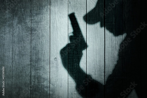 Photo Man with a gun in shadow on a wooden background