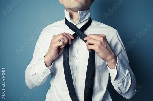 Obraz Young man tying his tie - fototapety do salonu