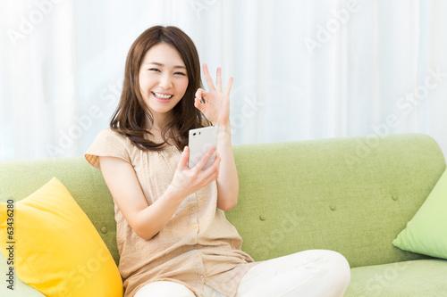 部屋でスマートフォンを見る女性 Canvas Print