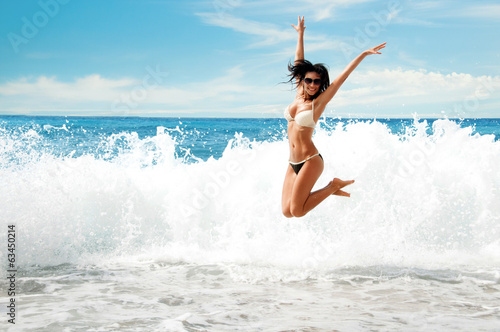 Photo  Beautiful young  girl  jumping on sea