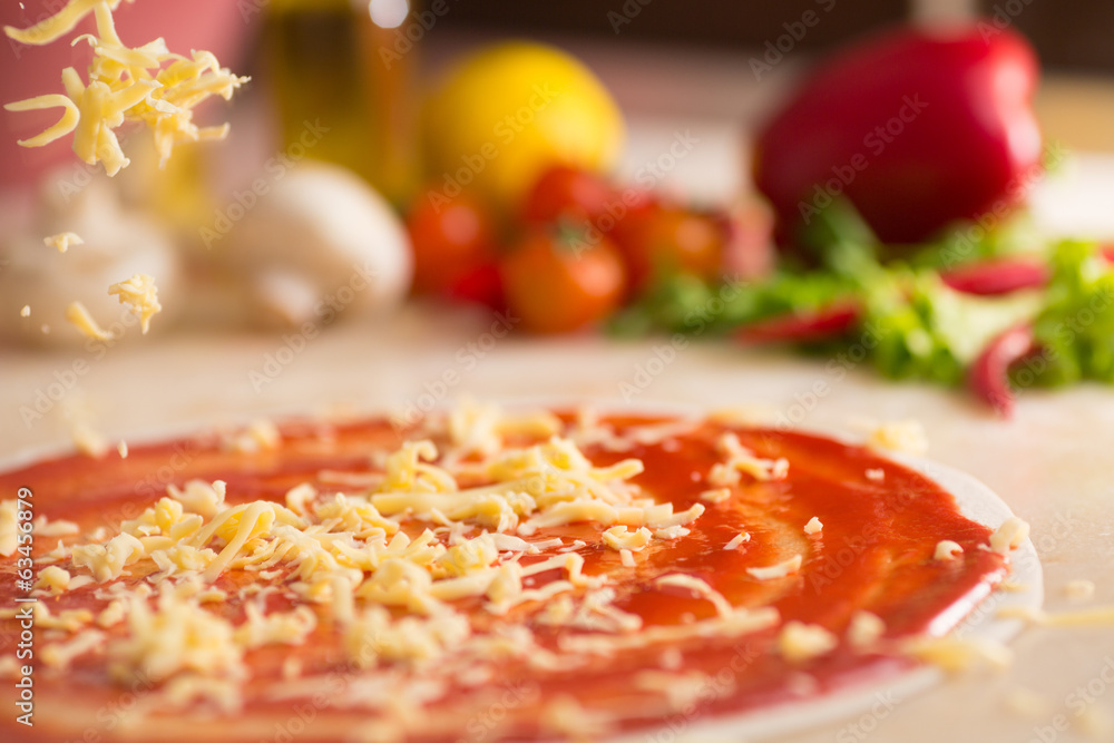 Italian pizza preparation with cheese falling.