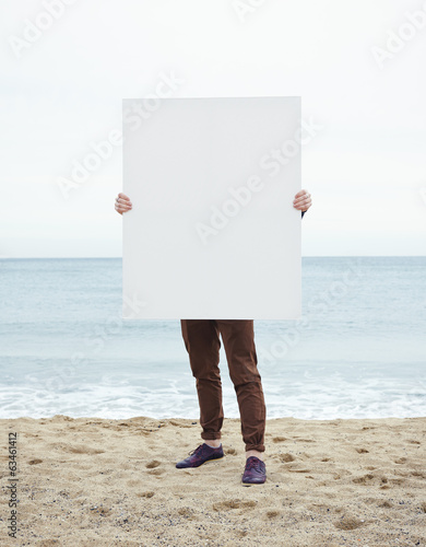 Man standing on a beach and holding blank poster