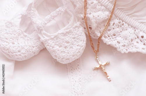 Fotografía Baby shoes and white dress with golden cross for Christening