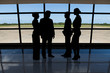 Businesspeople standing against airport window