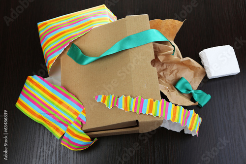 Fotografia, Obraz  Unwrapped and opened gift box  on wooden background