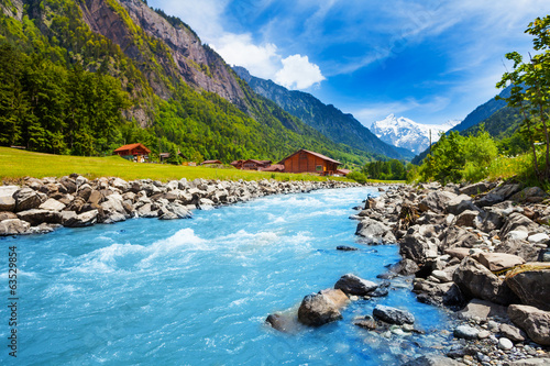 Foto op Plexiglas Blauw Swiss landscape with river stream and houses
